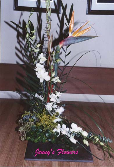 {I made this arrangement with Bird of Paradise, Orchid, and greens}