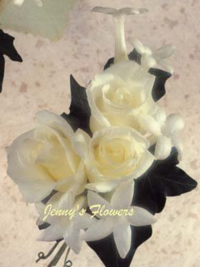{Fragrant Stephanotis blossom are pearlized with Bouvardia and Ming Fern and Camellia leaves in corsage}
