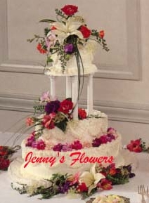 {Striking flowers sit at the top of the cake with a festive cluster placed in the middle.  Delicate petals are placed on the base layer with another striking cluster fashioned at the base.}