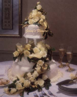 {Beautiful fondant wedding cake with white ivory roses form the top and continue to spill from layer to layer to the top of the table.  Rose petals surround the base of the cake}