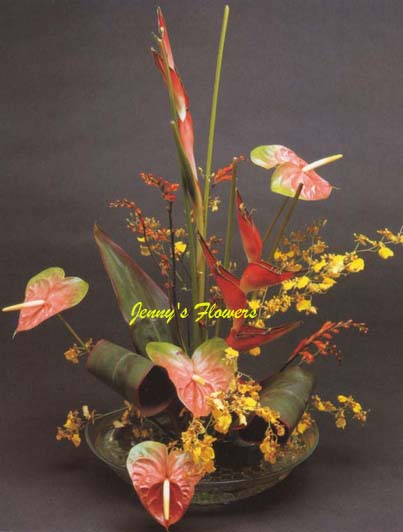 {Exotic flowers are combined to create lovely contemporary treatment of Oriental designs.  Materials include Heliconia, heart-shaped anthuriums, Oncidium orchids, the Montbretia, and Ti Leaves.}