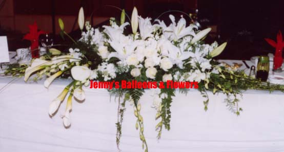 {Head Table with white Calla Lilies, White Lillies, orchid, Stock, ivy, and bear grass}