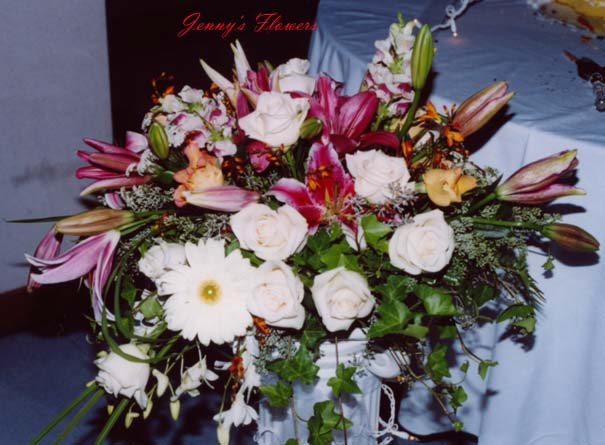 {Centerpiece with Oriental lilies, roses, orchids, Gerbera daisies, Ivy, Eucaplypus Seeds, and greens}