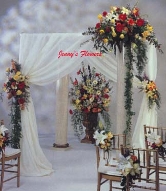 {Perfect for formal ceremonies.  Gerbera daisies, lilies, freesia, roses, carnations, and delphinium are flowers used for the floral accents.  Trails of sprengeri foliage and smilax garlands enhance the sweeping fabric background.}